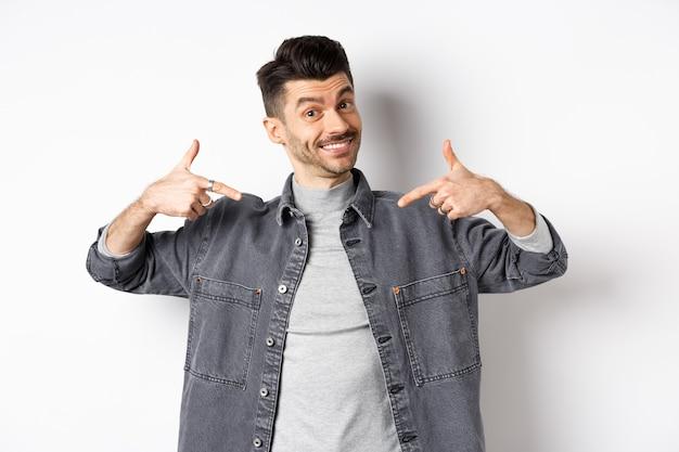 Cara bonito com bigode e sorriso branco apontando os dedos para o centro, mostrando o logotipo da empresa, de pé sobre um fundo branco.