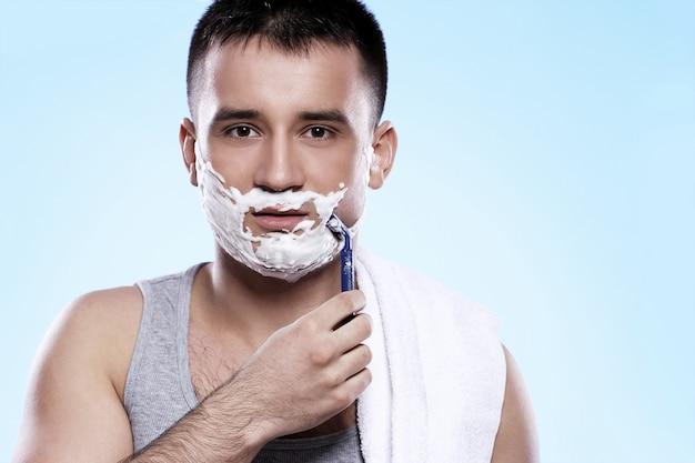 Cara bonito com espuma de barbear e navalha