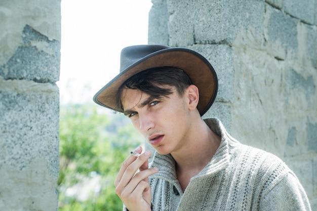 Cara bonito com rosto confiante. close-up jovem fumando um cigarro, charuto. homem bonito usa chapéu de cowboy.