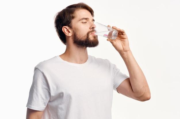 Cara bonito com um copo de água em uma t-shirt de parede branca vista recortada modelo.