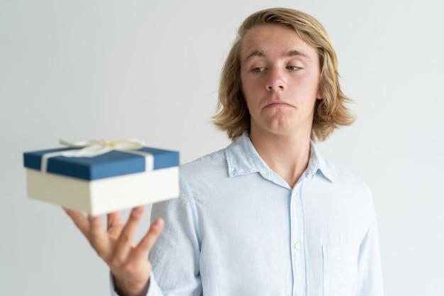 Cara bonito confuso decepcionado com tamanho de caixa de presente