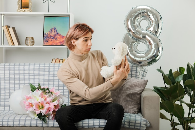 Cara bonito confuso no dia da mulher feliz segurando e olhando para o ursinho de pelúcia sentado no sofá na sala de estar