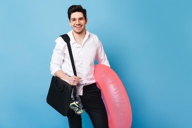 Cara bonito de camisa branca está segurando a bolsa para laptop. homem de óculos posando com círculo inflável e máscara de mergulho no espaço azul.