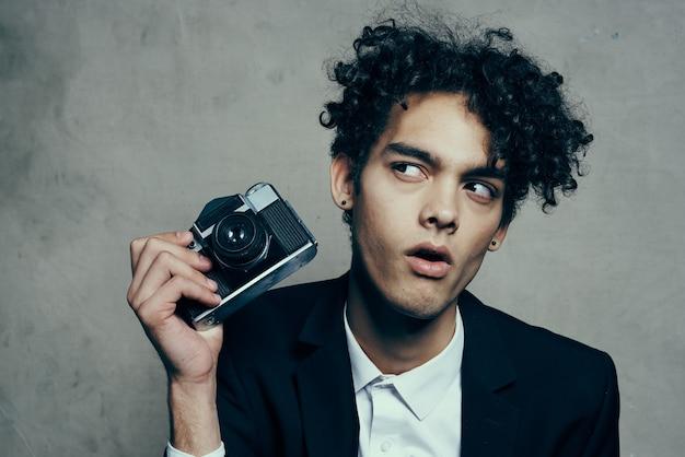 Cara bonito de terno com uma câmera aulas modelo de emoções de cabelo encaracolado