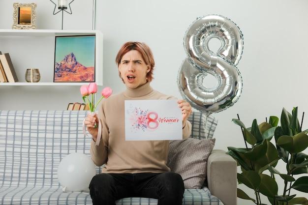 Cara bonito descontente no feliz dia das mulheres segurando flores com um cartão de felicitações, sentado no sofá da sala de estar