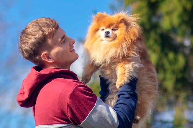 Cara bonito, dono de jovem adorável com cachorro pomeranian spitz, cachorrinho doce bonito nas mãos. as pessoas adoram animal de estimação, conceito de animal. garoto espera, abraça seu lindo cachorro, sorrindo. copie o espaço