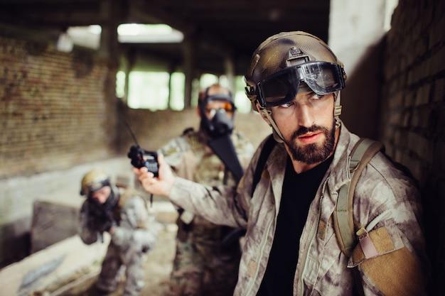 Cara bonito e barbudo está inclinado para a parede e olhando direito. ele é cuidadoso. o homem parou seus soldados de atacar. eles estão esperando.