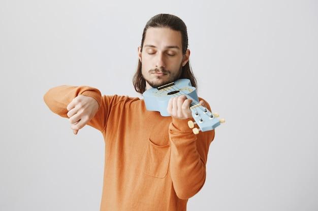 Cara bonito e engraçado segurando o ukulele como um violino