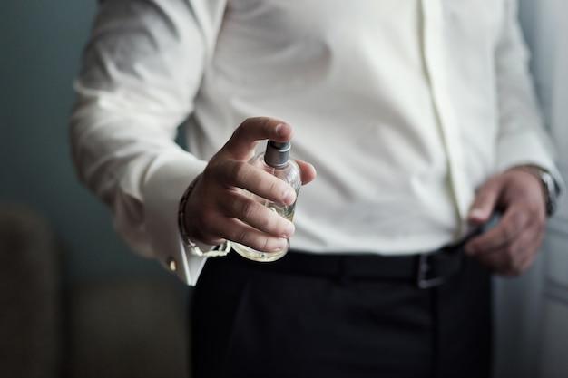 Cara bonito é escolher perfumes, homem elegante de terno usando colônia, noivo se preparando a manhã antes da cerimônia de casamento