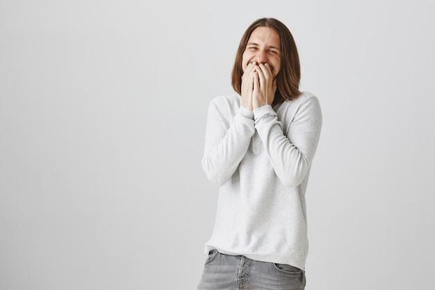 Cara bonito e feliz rindo de uma piada, tapando a boca