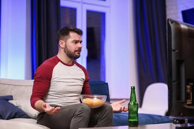 Cara bonito e moderno, positivo, com barba bem preparada, saboreando chips durante a revisão emocional do jogo do time de futebol favorito na tv em casa