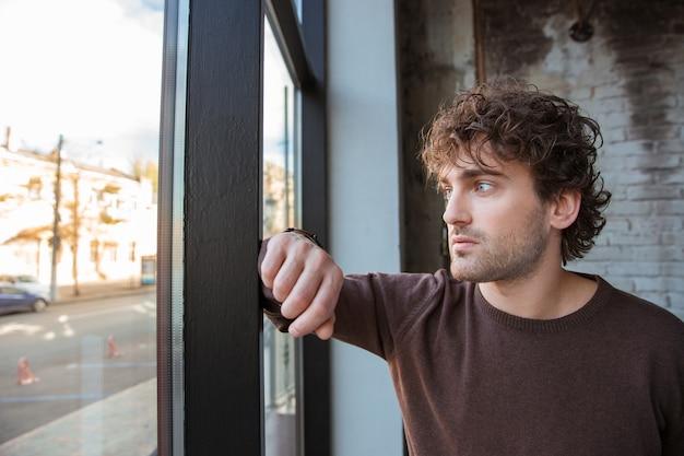 Cara bonito e pensativo em um moletom marrom olhando para a janela