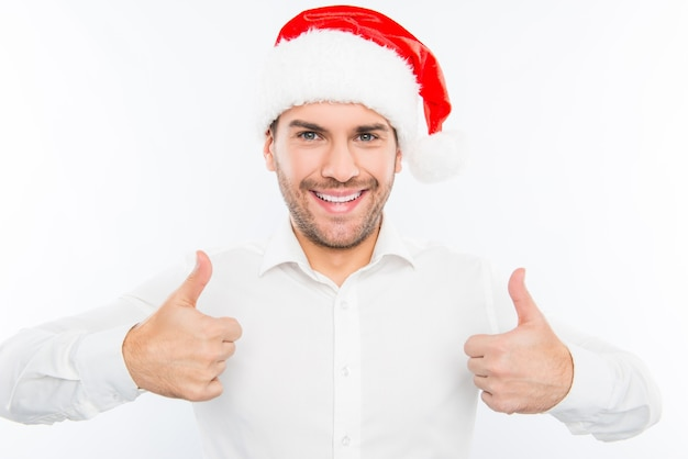 Cara bonito e sorridente com chapéu de papai noel mostrando os polegares para cima