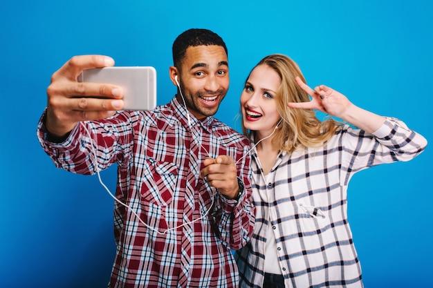 Cara bonito elegante fazendo selfie retrato com mulher jovem e atraente com longos cabelos loiros. divertir-se, ouvir música pelos fones de ouvido, bom humor, relaxar.