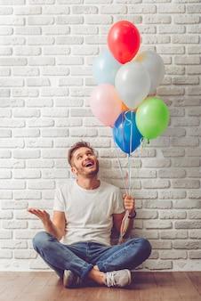 Cara bonito em roupas casuais está segurando balões.