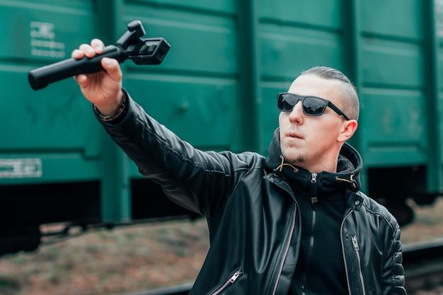 Cara bonito em roupas pretas e óculos de sol fazendo selfie ou streaming de vídeo usando a câmera de ação com estabilizador de câmera gimbal na ferrovia