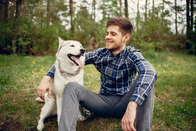 Cara bonito em um parque de verão com um cachorro