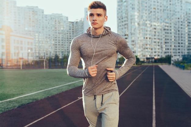 Cara bonito em um terno esporte cinza está executando um treino de manhã no estádio. ele está ouvindo música com fones de ouvido e olhando para o lado.