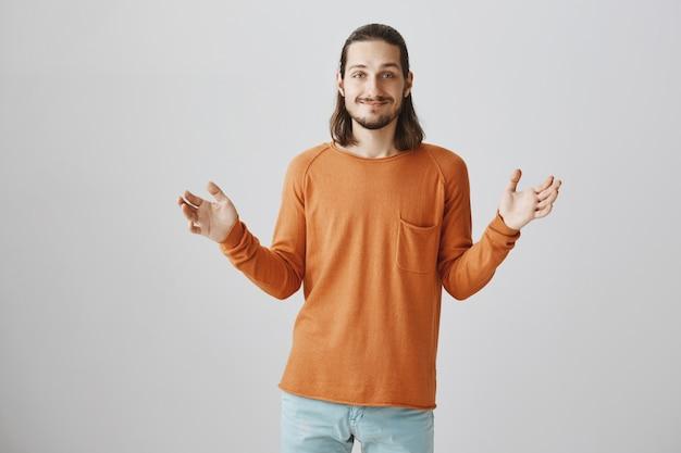 Cara bonito hipster mostrando um grande objeto, sorrindo feliz