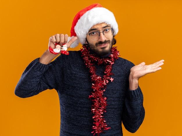 Cara bonito jovem descontente com chapéu de natal com guirlanda no pescoço, segurando brinquedos, espalhando mão isolada em fundo laranja