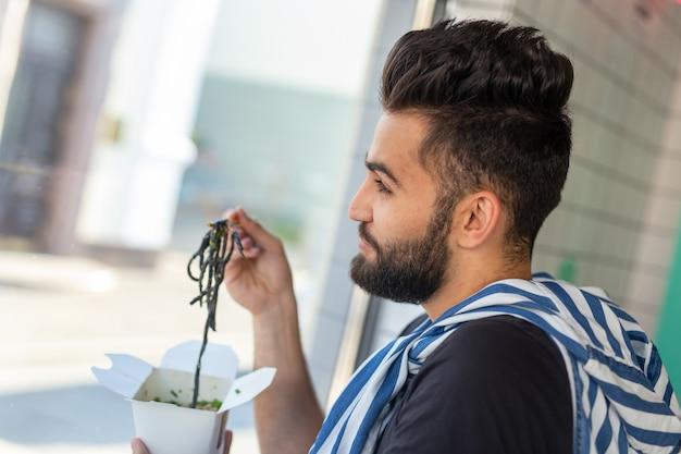 Cara bonito jovem hippie comendo macarrão chinês usando pauzinhos de madeira, sentado em um café e olhando pela janela. conceito de cozinha asiática.