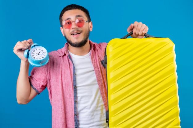 Cara bonito jovem viajante usando óculos escuros, segurando a mala de viagem e despertador, olhando feliz e positivo em pé sobre fundo azul