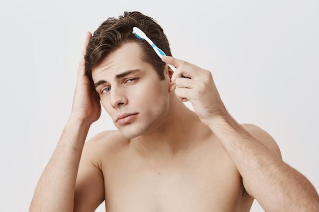 Cara bonito musculoso com penteado da moda, pele saudável, fazendo caretas, se divertindo dentro de casa, usando a escova de dentes para pentear o cabelo escuro. modelo masculino nu atraente olhando com apelo