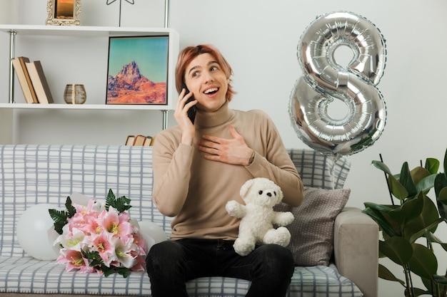 Cara bonito no dia da mulher feliz segurando o ursinho de pelúcia falando ao telefone, sentado no sofá na sala de estar