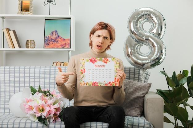 Cara bonito no feliz dia da mulher segurando e apontando para o calendário sentado no sofá na sala de estar