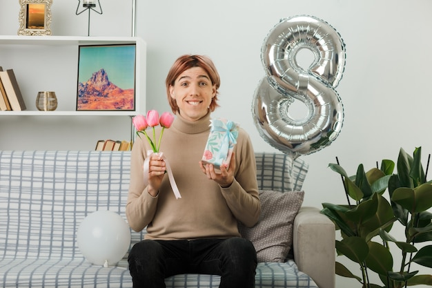 Cara bonito no feliz dia da mulher segurando flores com um presente sentado no sofá na sala de estar