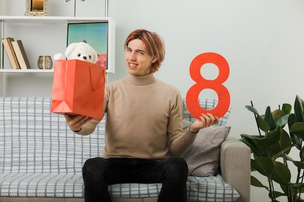 Cara bonito no feliz dia da mulher segurando o número oito com uma sacola de presente para a câmera, sentado no sofá da sala