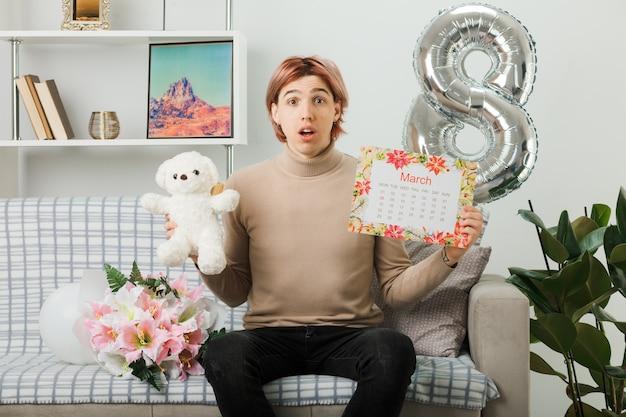 Cara bonito no feliz dia da mulher segurando o ursinho de pelúcia com calendário sentado no sofá na sala de estar