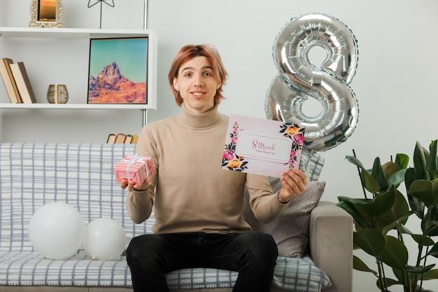 Cara bonito no feliz dia da mulher segurando um presente com um cartão postal sentado no sofá na sala de estar