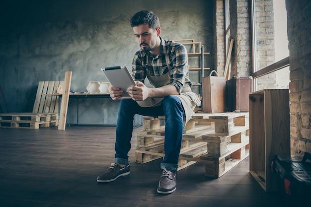 Cara bonito segurando e-book administrador do site lendo novos pedidos, verificando e-mail hora do jantar negócios de madeira indústria de marcenaria garagem interna