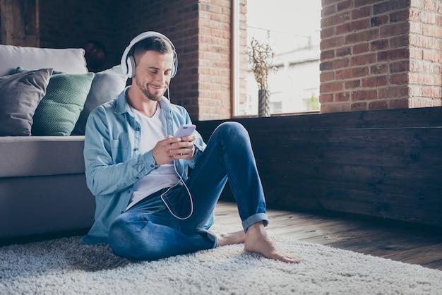 Cara bonito sentado confortável em um tapete fofo navegando no telefone