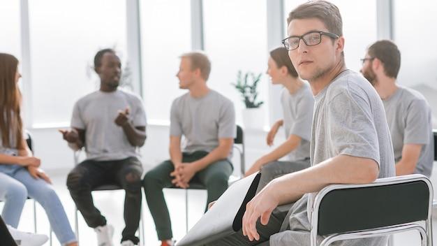 Cara bonito sentado em um círculo com uma pessoa de mentes semelhantes. negócios e educação