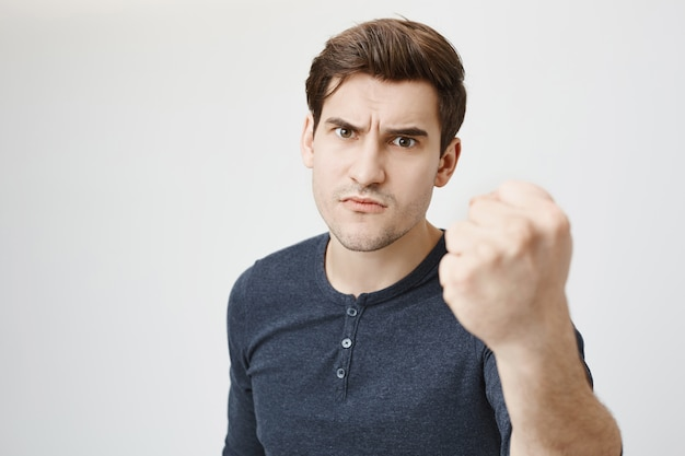 Cara bonito sério incomodado ameaça com o punho, repreendendo por mau comportamento