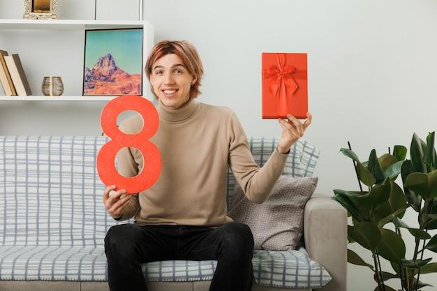 Cara bonito sorridente no feliz dia da mulher segurando o número oito com um presente sentado no sofá da sala de estar