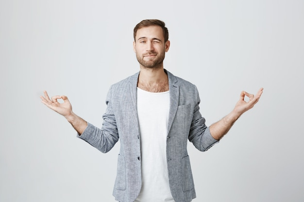 Cara bonito tentando meditar, espreitar durante a sessão de ioga