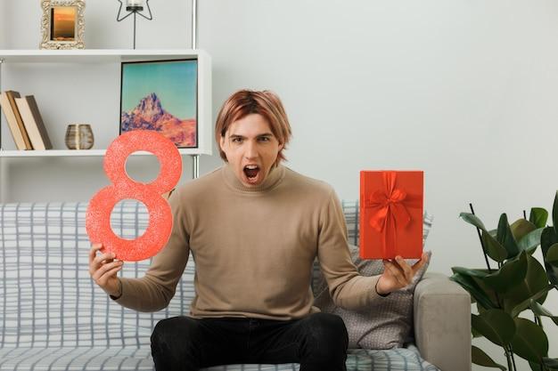Cara bonito zangado no dia da mulher feliz segurando o número oito com um presente sentado no sofá da sala de estar