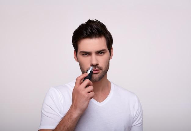 Cara branco bonito com um aparador na mão remove o cabelo no nariz.