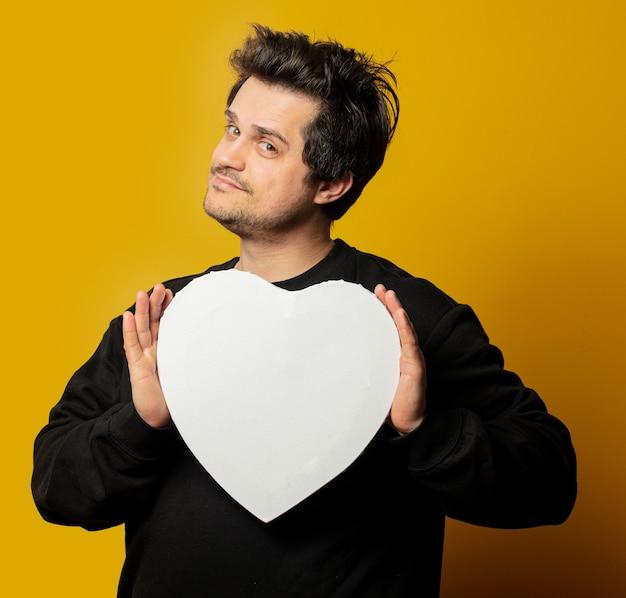 Cara branco surpreso em uma maquete de formato de coração de camisa preta