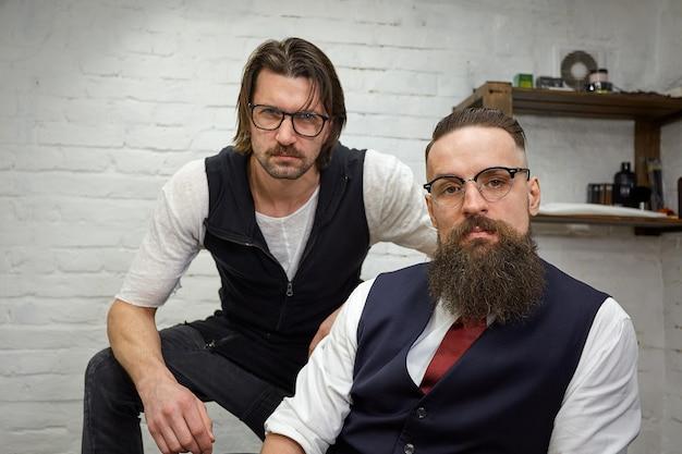 Cara brutal na barbearia moderna. cabeleireiro faz penteado um homem com barba. retrato de barba de homem elegante.