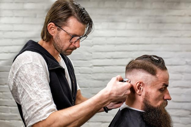 Cara brutal na barbearia moderna. cabeleireiro faz penteado um homem com uma barba longa. mestre cabeleireiro faz penteado com máquina de cortar cabelo