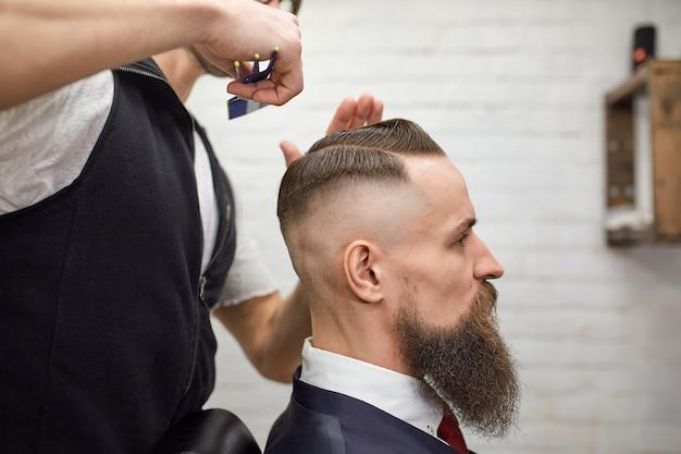 Cara brutal na barbearia moderna. cabeleireiro faz penteado um homem com uma barba longa. mestre cabeleireiro faz penteado por tesoura e pente