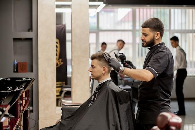 Cara brutal na barbearia moderna. cabeleireiro faz penteado um homem. mestre cabeleireiro faz penteado com máquina de cortar cabelo. barbearia