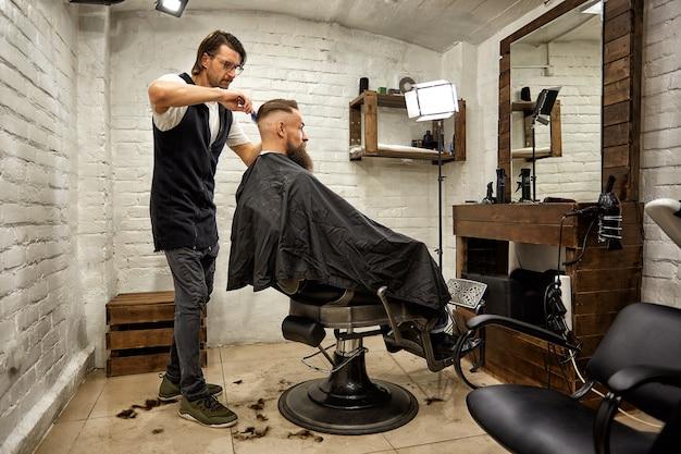 Cara brutal na barbearia moderna o cabeleireiro faz o penteado de um homem com uma barba retrato de um homem elegante barba o cabeleireiro mestre faz penteado e estilo com tesouras e pente