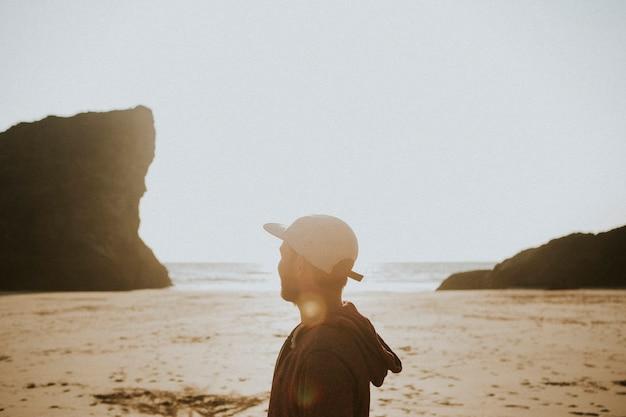 Cara caminhando em uma praia ensolarada