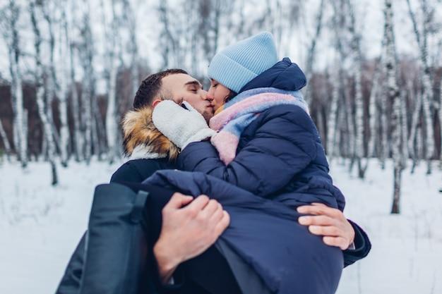Cara carregando a namorada nas mãos e beijando na floresta de inverno. pessoas se divertindo ao ar livre