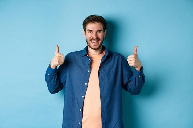 Cara caucasiano alegre na camisa casual, mostrando os polegares em aprovação, sorrindo e elogiando algo bom, de pé sobre fundo azul.